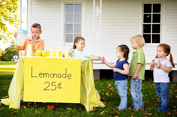 Children at a Lemonade Stand Color photo of a young boy and girl serving neighborhood kids at their lemonade stand. lemonade stand stock pictures, royalty-free photos & images