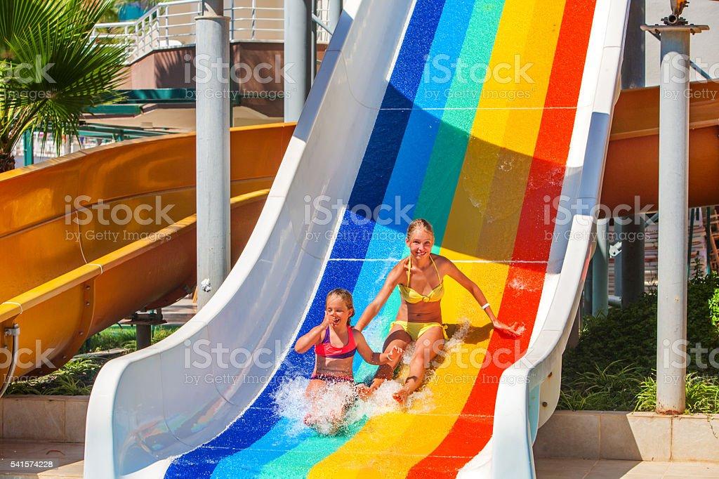 children at aquapark slide down water slides. stock photo