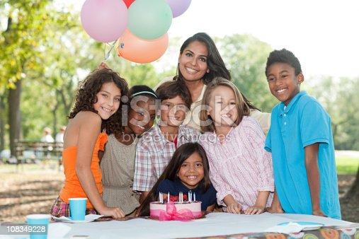 istock Children at birthday party with birthday cake 108349228