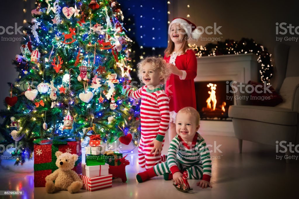 Children At Christmas Tree Kids At Fireplace On Xmas Eve Stock Photo Download Image Now Istock