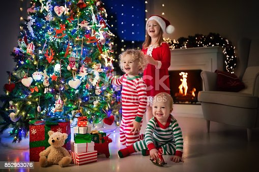 869520896 istock photo Children at Christmas tree. Kids at fireplace on Xmas eve 852953076