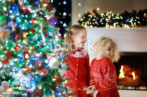 1068864298 istock photo Children at Christmas tree. Kids at fireplace on Xmas eve 865424668
