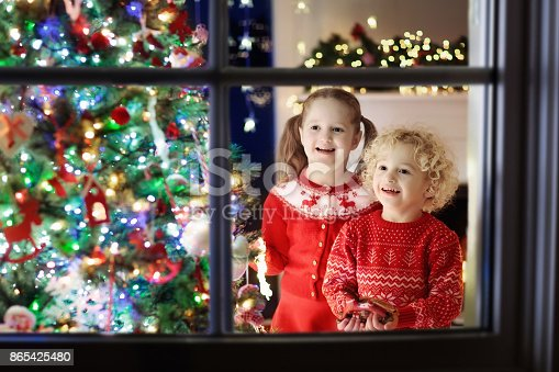 1068864298 istock photo Children at Christmas tree. Kids at fireplace on Xmas eve 865425480