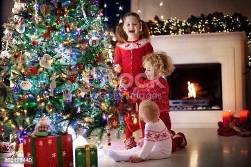1068864298 istock photo Children at Christmas tree. Kids at fireplace on Xmas eve 865428440