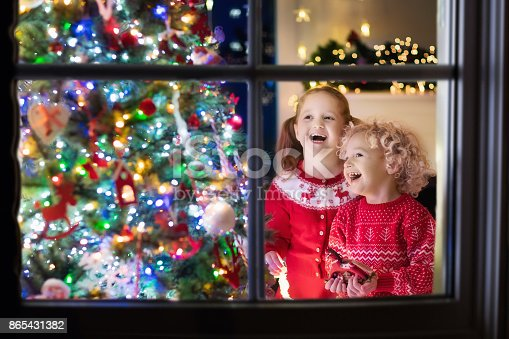 1068864298 istock photo Children at Christmas tree. Kids at fireplace on Xmas eve 865431382