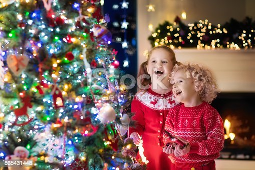 1068864298 istock photo Children at Christmas tree. Kids at fireplace on Xmas eve 865431448