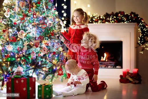 1068864298 istock photo Children at Christmas tree. Kids at fireplace on Xmas eve 865431568