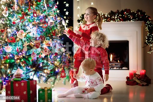1068864298 istock photo Children at Christmas tree. Kids at fireplace on Xmas eve 865432344