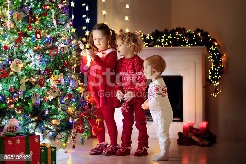1068864298 istock photo Children at Christmas tree. Kids at fireplace on Xmas eve 865432422