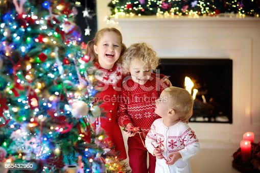 869520896 istock photo Children at Christmas tree. Kids at fireplace on Xmas eve 865432960