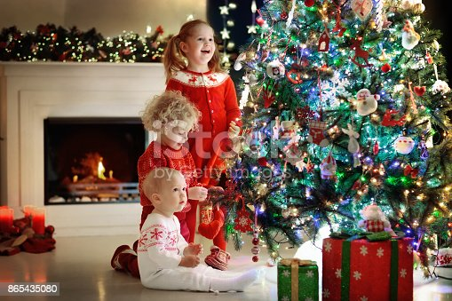 1068864298 istock photo Children at Christmas tree. Kids at fireplace on Xmas eve 865435080