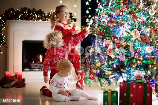 869520896 istock photo Children at Christmas tree. Kids at fireplace on Xmas eve 867924948