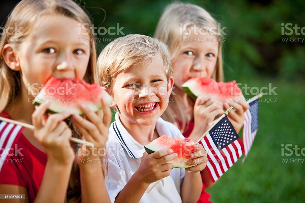 Children at Fourth of July or Memorial Day picnic A group of three children at a picnic on July 4th or Memorial day. They are sitting, eating watermelon and holding small American flags.  They are siblings from the same family, a brother and two older sisters, all with blond hair.  The girls are wearing red shirts and the boy is wearing a white shirt with a blue stripe on his collar.  The focus is on the little boy, who is sitting in the middle with a big grin on his smiling face as he looks at the camera.  He is 4 years old. 4-5 Years Stock Photo