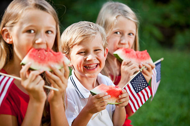 Children at Fourth of July or Memorial Day picnic A group of three children at a picnic on July 4th or Memorial day. They are sitting, eating watermelon and holding small American flags.  They are siblings from the same family, a brother and two older sisters, all with blond hair.  The girls are wearing red shirts and the boy is wearing a white shirt with a blue stripe on his collar.  The focus is on the little boy, who is sitting in the middle with a big grin on his smiling face as he looks at the camera.  He is 4 years old. independence day photos stock pictures, royalty-free photos & images
