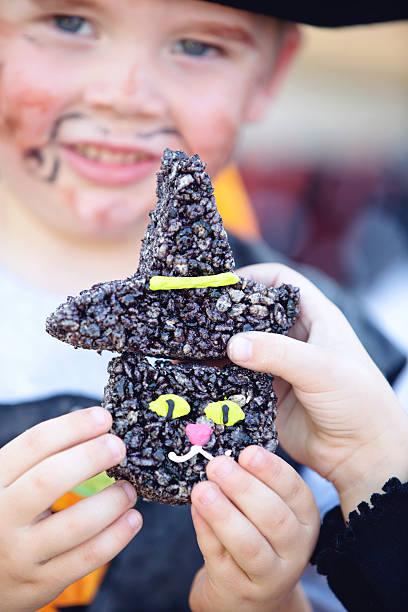 kinder in halloween-party hält süßigkeiten - piratenparty snacks stock-fotos und bilder