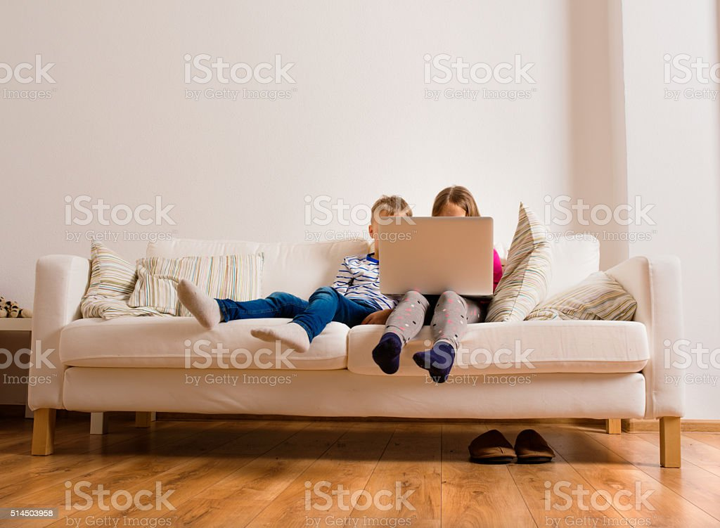 Children at home sitting on sofa, playing with laptop stock photo