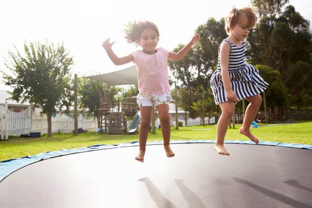 niños en la escuela montessori que se divierten en trampolín al aire libre - trampolín artículos deportivos fotografías e imágenes de stock