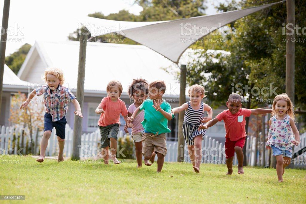 Children At Montessori School Having Fun Outdoors During Break stock photo
