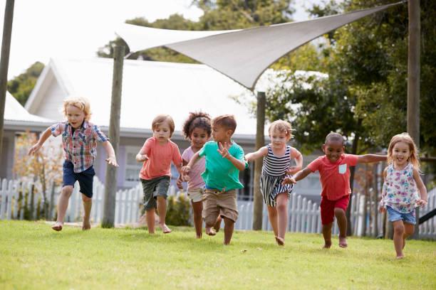 children at montessori school having fun outdoors during break - preschool student stock photos and pictures