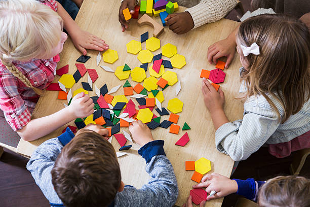 children at preschool playing with colorful shapes - blok vorm stockfoto's en -beelden