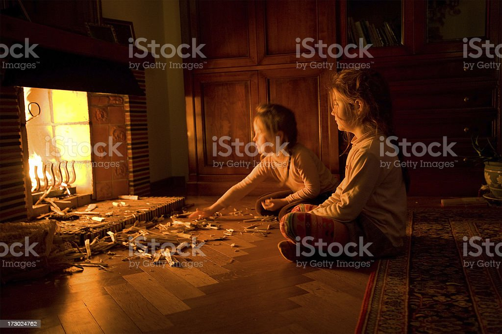 Children at the fireplace Two young children at the fireplace, aged 5 and 7. 4-5 Years Stock Photo