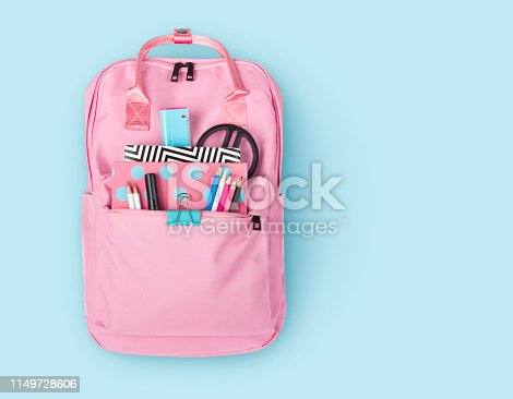 Children backpack with various school stationery isolated on blue background