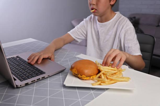 filhos maus hábitos alimentares, garoto comer insalubre junk food e jogos de computador - junk food - fotografias e filmes do acervo