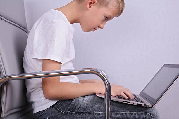 children bad incorrect sitting posture. boy using laptop computer - postawa zdjęcia i obrazy z banku zdjęć