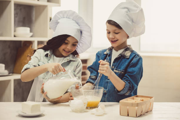 children baking in kitchen - kids cooking stock photos and pictures