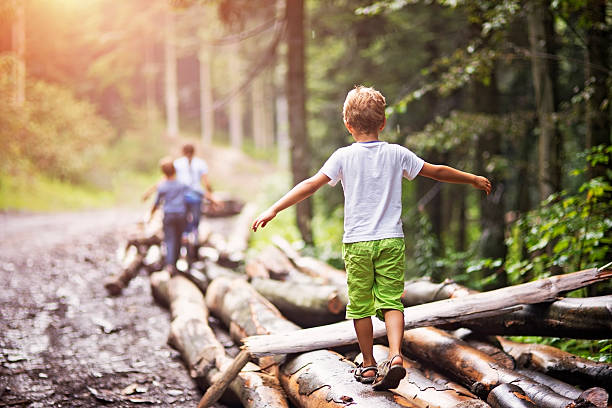 Children balancing on tree trunks Little hikers walking on a tree trunks in a forest. balance stock pictures, royalty-free photos & images