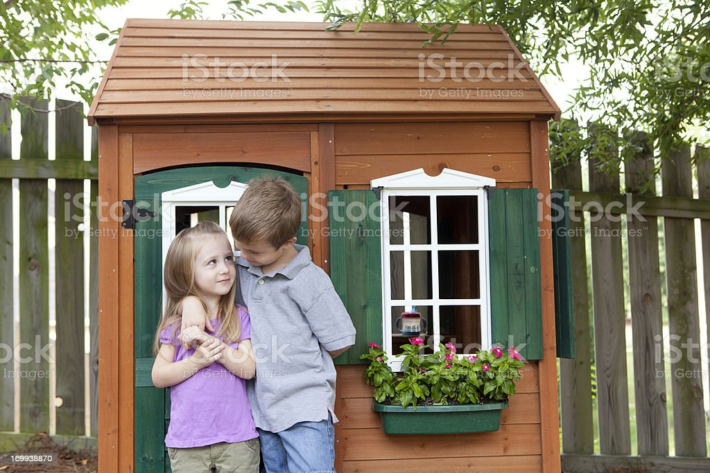 Children being friendly in front of wooden playhouse stock photo