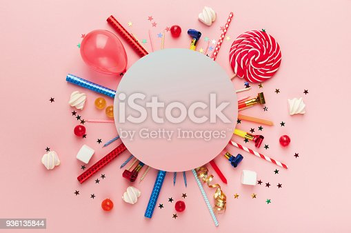 Children birthday party background, frame with sweets, lollipops and confetti on pink background, copy space, top view