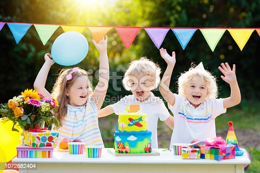 istock Children blow candles on birthday cake. Kids party 1072682404