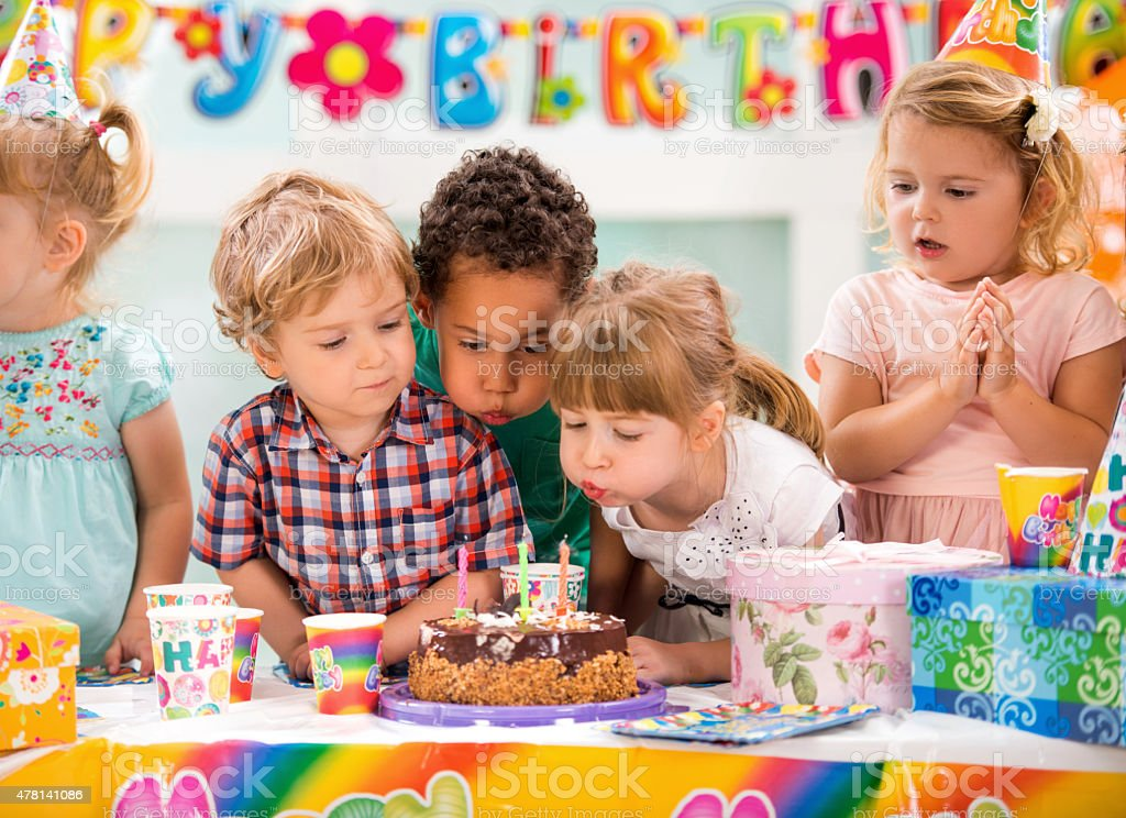 Children blowing birthday candles on birthday party. stock photo