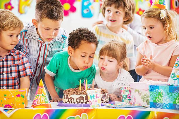 kinder blasen geburtstag kerzen. - kindergeburtstagskuchen stock-fotos und bilder