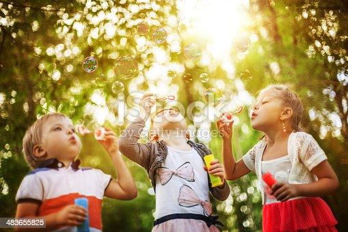 618034312 istock photo Children blowing bubbles 483655825