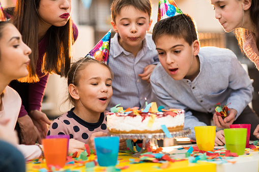 Group of children and an adult woman standing around the cake wearing party hats and feeling positive
