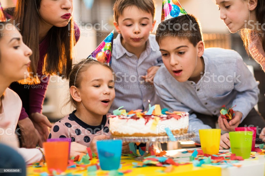 Children Blowing candles on a Birthday party stock photo