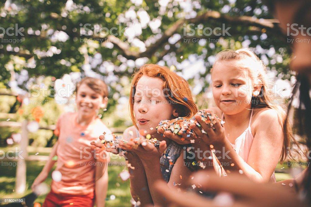 Children blowing colourful confetti in a sunny park stock photo