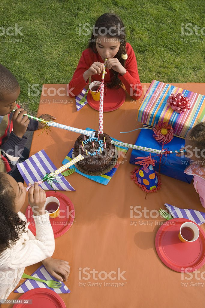 Children (5-10) blowing party blowers at birthday cake, elevated view royalty-free stock photo