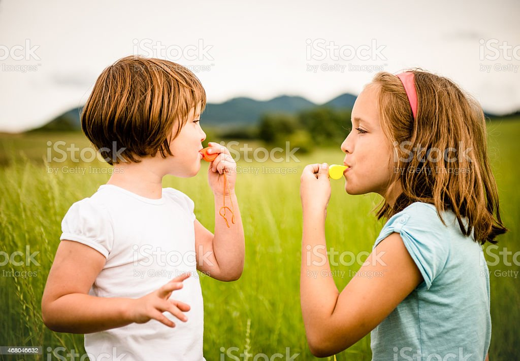 Children blowing whistle stock photo