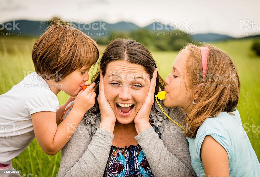 Children blowing whistle to mother's ears stock photo