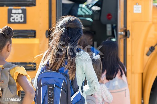 A line of school children with obscured faces board a school bus on their way to school.