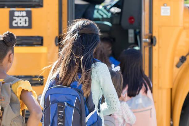 kinderen aan boord van een schoolbus in een lijn - verduisterd gezicht stockfoto's en -beelden