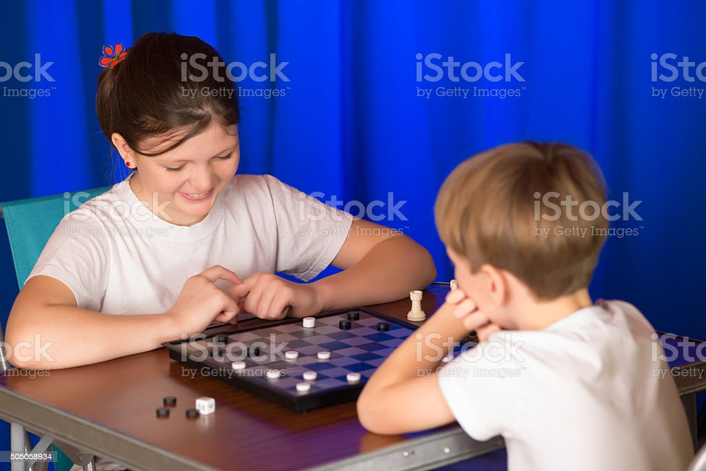 Children boy and girl playing a board game called Checkers stock photo