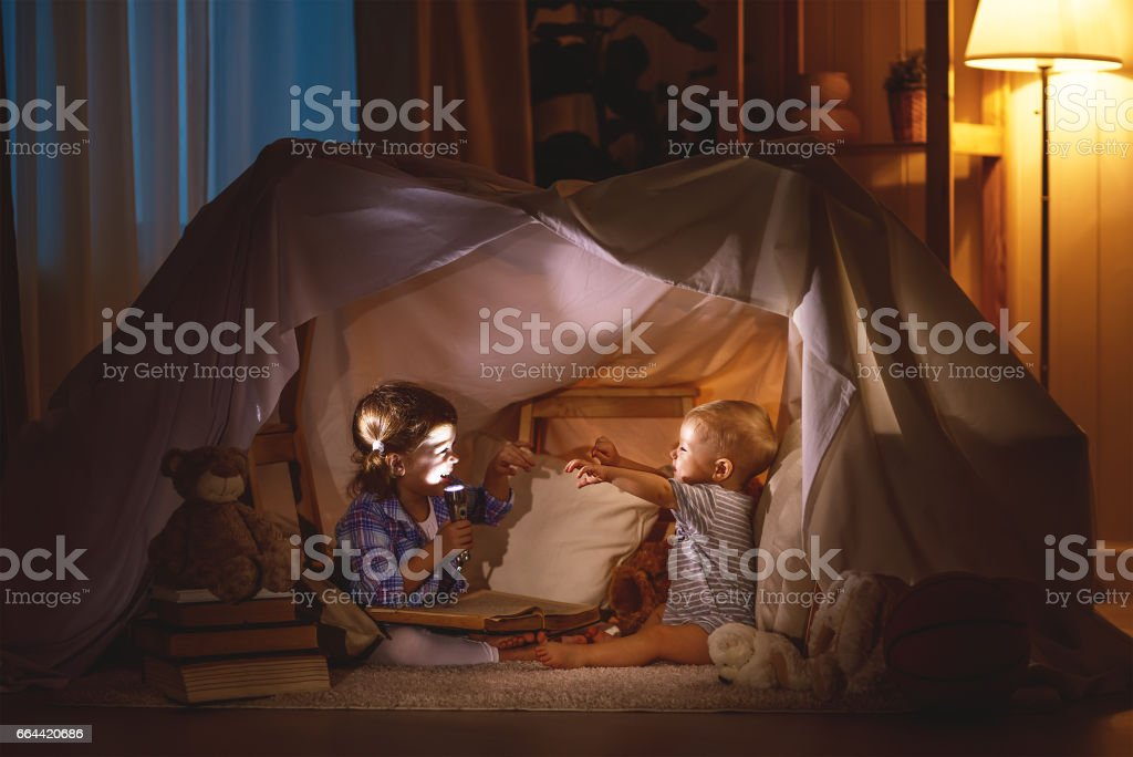children boy and girl playing and frighten each other in  tent stock photo
