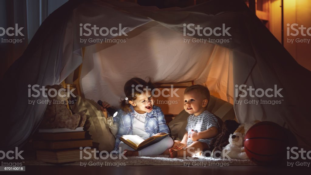 children boy and girl reading book with  flashlight in  tent stock photo