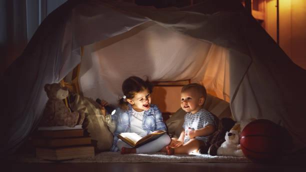 kinder jungen und mädchen lesebuch mit taschenlampe im zelt - deckenleuchte kinderzimmer stock-fotos und bilder
