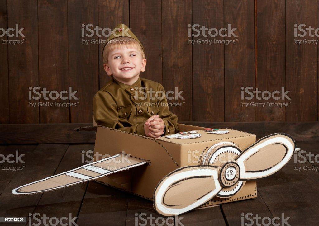 Junge Kinder sind verkleidet als Soldat in Retro-Militäruniformen sitzen in einem Flugzeug von Karton und träumt davon, ein pilot, dunklen Holz Hintergrund, Retro-Stil gemacht - Lizenzfrei Alt Stock-Foto