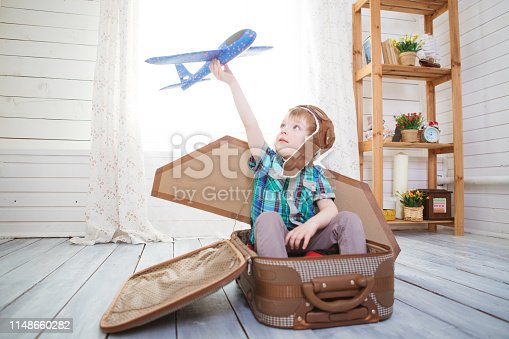 Children boy wearing pilot costume making ready to fly gesture standing on living room wooden floor at home.